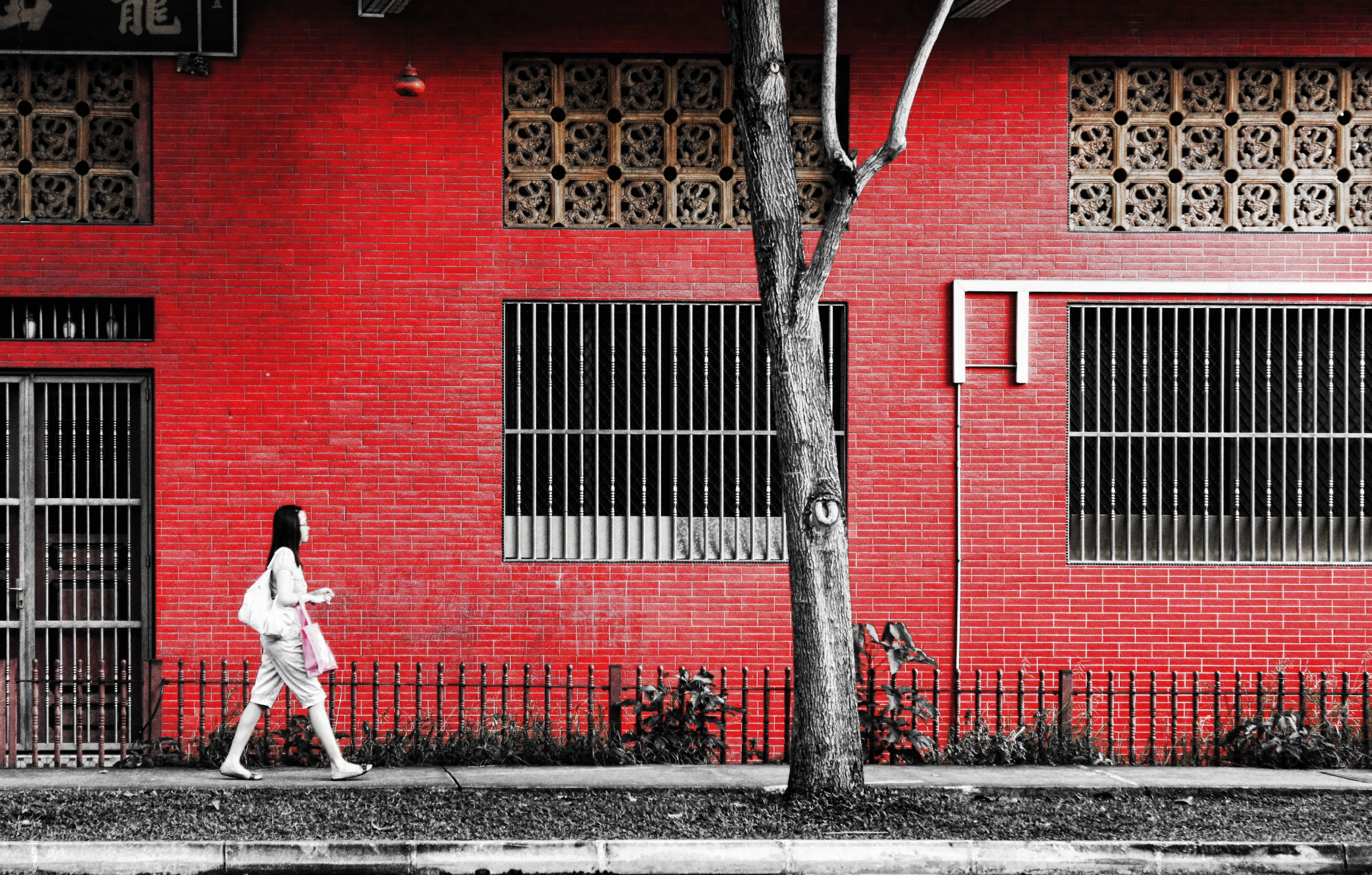 girl walking by red building ashton morris